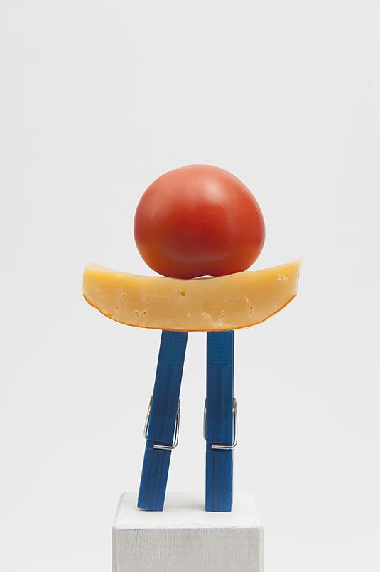 Tijdelijke sculptuur met rode tomaat, gele kaas en blauwe wasknijpers