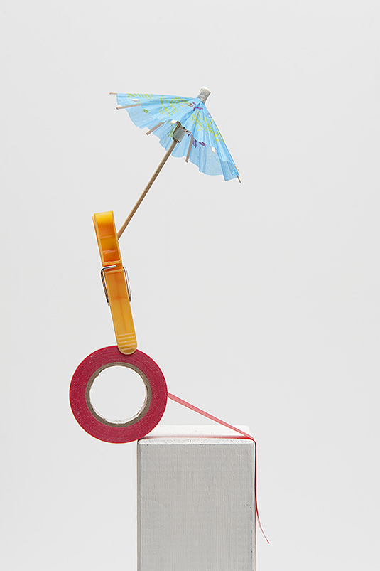 Tijdelijke sculptuur met rode rol tape, gele wasknijper en blauwe parasol