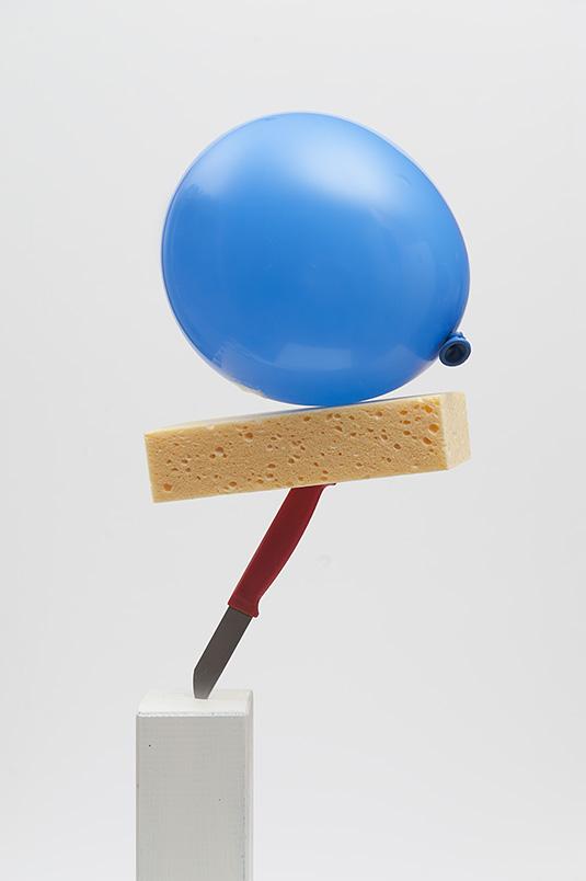 Tijdelijke sculptuur met rood keukenmesje, gele spons en blauwe ballon