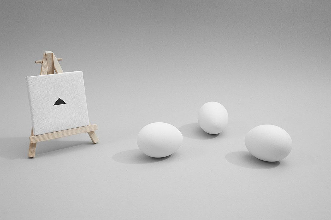 miniatuur canvas met zwarte driehoek op schildersezel met drie eieren in een driehoek