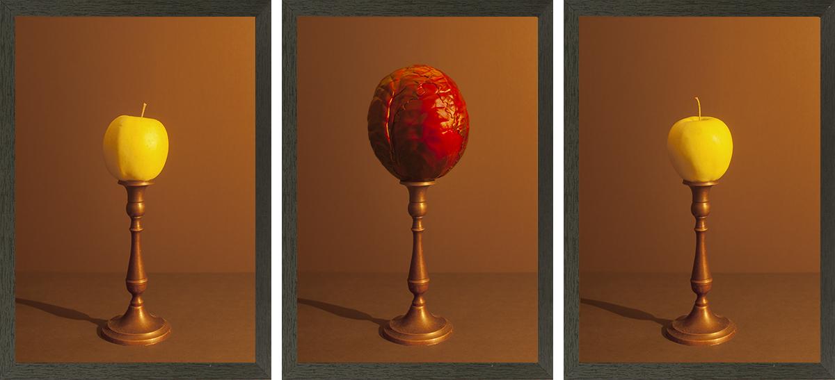 drieluik bestaande uit twee appels en een rode kool belicht met kaarslicht