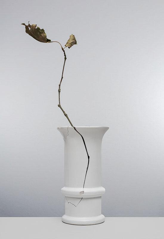 gebroken witte vaas met scheur waar een takje uitsteekt met verdorde blaadjes