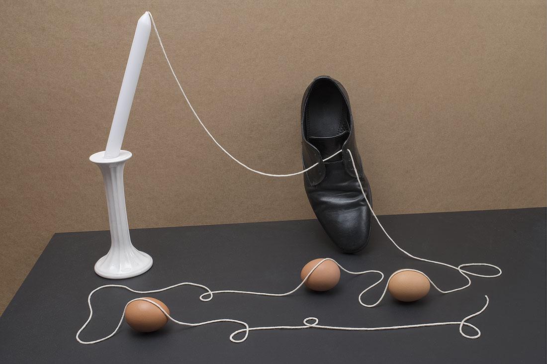 witte draad die vanuit een kaars door een schoen gaat en over drie eieren valt