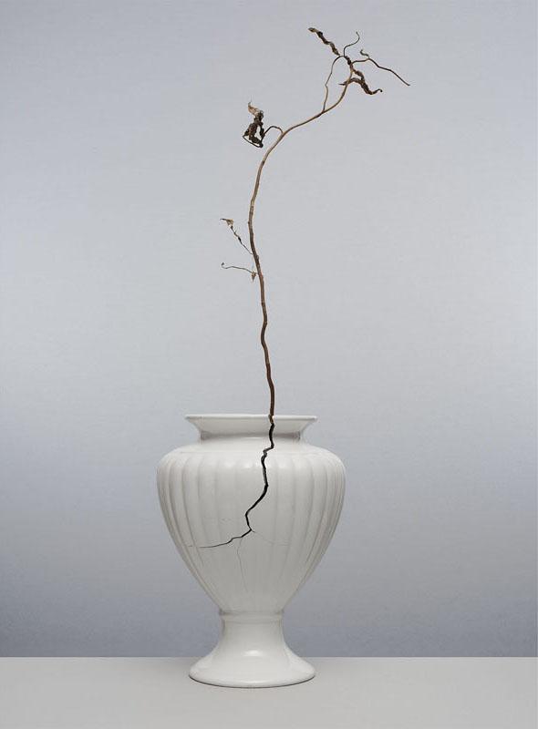 gebroken witte vaas met scheur waar een takje uitsteekt